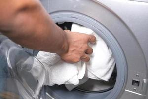 närbild av en person som laddar tvättmaskinen foto