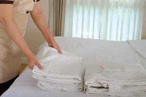 ung städerska ordna handduk och göra sängen i hotellrummet foto