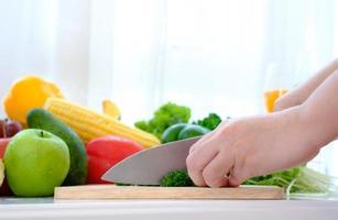 händer med en kniv hugga grönsaker över träsnideri foto