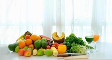 diverse färska mogna frukter och grönsaker på bordet med vit gardinbakgrund foto