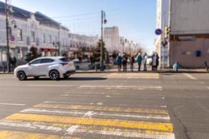 stadslandskap av ett övergångsställe med suddiga människor, bilar och byggnader i Vladivostok, Ryssland foto