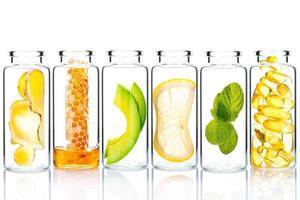 alternativ hudvård och hemlagad skrubb med naturliga ingredienser i glasflaskor isolerad på vit bakgrund foto