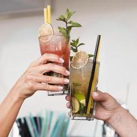 närbildkvinnor som tycker om cocktailglas foto