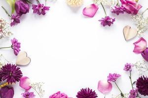 olika blommor med trähjärtor inramat bord foto