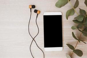 hörlurar och mobiltelefon med löv på träbakgrund foto