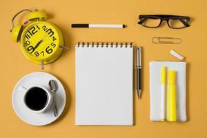 platt låg anteckningsbok kaffekopp på gul bakgrund foto