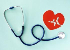 platt låg stetoskop med papper hjärta på blå grön bakgrund foto