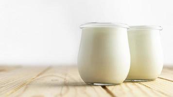 framifrån av vanlig yoghurt i burkar med naturlig belysning foto