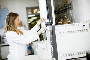 kvinnlig vetenskapsman i en vit labbrock sätter flaskan med ett prov för en analys på en gaskromatograf i biomedicinskt laboratorium foto