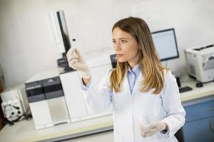 kvinnlig forskare i en vit labrock förbereder flaskan med ett prov för en analys på en gaskromatograf i biomedicinskt laboratorium foto