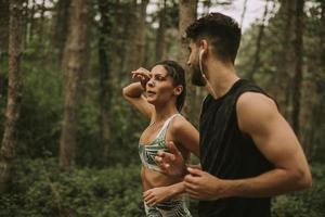 unga fitnesspar som kör på skogsstigen foto