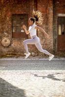 ung kvinna juping högt under träning i stadsmiljön foto