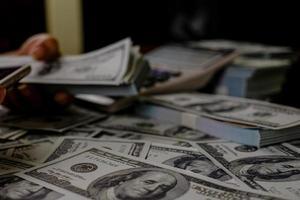 hand räknar pengar på en bunt med 100 dollar sedlar foto