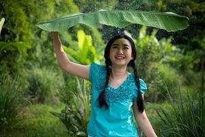 asiatisk kvinna med svart hår som håller ett bananblad i regnet foto