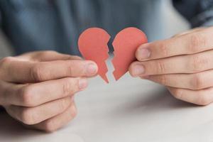 närbild händer som håller papper trasigt hjärta foto