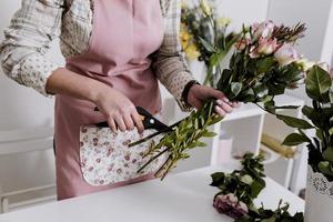 beskuren blomsterhandlare som förbereder blommor foto
