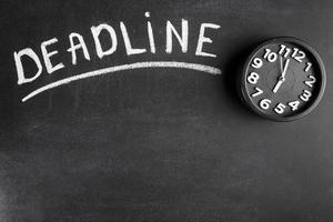 deadline text svart tavla med väckarklocka på svart bakgrund foto