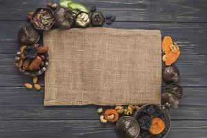 olika torkade frukter med nötter som gränsar till duk på träbakgrund foto