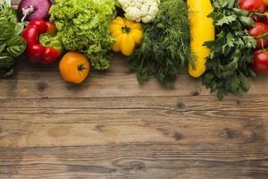 platt låg grönsaker sortiment på trä bakgrund foto