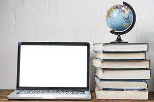 världen och böcker nära bärbar dator på ett bord foto