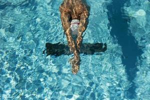 manlig simmare i hög vinkel i poolen foto