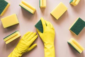 närbild person med gula handskar svampar foto