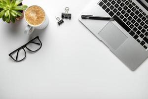 platt låg skrivbord med bärbar dator och glasögon foto