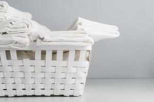 framifrån av en vit korg med handdukar foto
