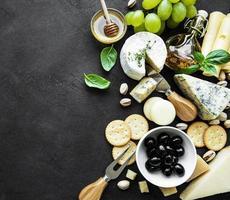 ovanifrån av ost, druvor, honung, och andra snacks foto