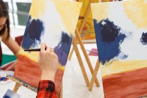 närbild av kvinnlig konstnär hand måla en bild på en palett på verkstaden foto