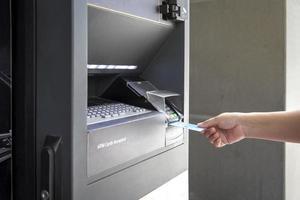 närbild av kvinnlig hand med kreditkort på en bankomat för att ta ut pengar foto