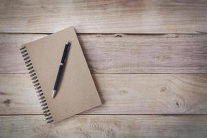 ovanifrån av bok med tomma sidor och penna på träbakgrund foto