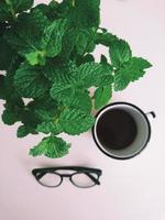 en kopp kaffe med glasögon och gröna bladväxter foto