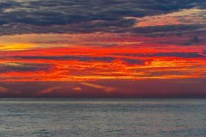 färgrik orange och röd solnedgång över en vattensamling foto