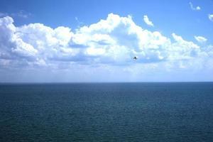 marinmålning av vattnet och himlen med svullna vita moln foto