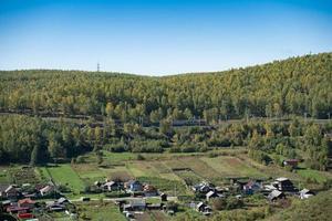 Flygfoto över byn kultuk med en klarblå himmel i Ryssland foto