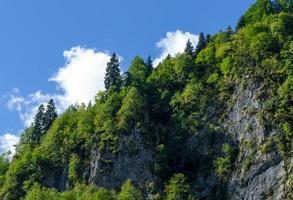 landskap med berg och skogar med en molnig blå himmel i abchazien foto