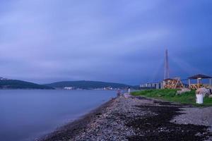 utsikt över stenig strandlinje med russky bridge i bakgrunden och en vattendrag i Vladivostok, Ryssland foto