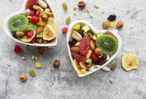två hjärtformade skålar med torkad frukt och nötter foto