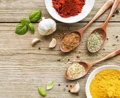 kryddor på ett träbord i skålar och skedar foto