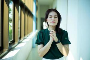 asiatisk kvinna som ber på morgonen nära fönstret i kyrkan, händerna vikas i bön koncept för tro, andlighet och religion, kyrkans tjänster online koncept. foto