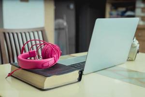 bärbar dator på ett bord med rosa hörlurar foto