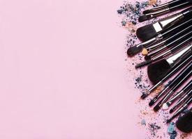 sminkborstar med kopieringsutrymme på en rosa bakgrund foto