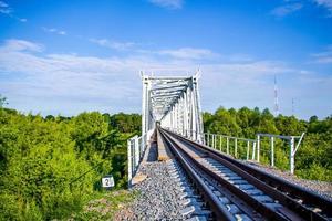 vacker järnvägsbro på en bakgrund av grönska och blå himmel, perspektiv foto