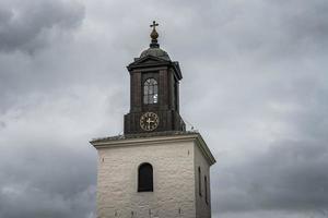 gammalt kyrktorn mot en mörk molnig himmel foto