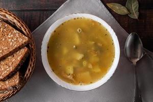 fisksoppa i en tallrik på en brun bakgrund foto