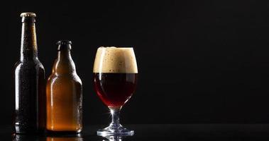 öl med skum på svart bakgrund foto