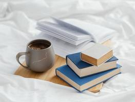 kaffe med böcker och kopp i sängen foto