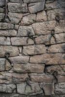 gammal stenvägg med järnförstärkningsöglor foto