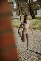 ganska ung kvinna som sträcker sig under träning i stadsmiljön foto
